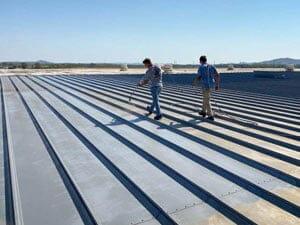 applying primer to metal roof